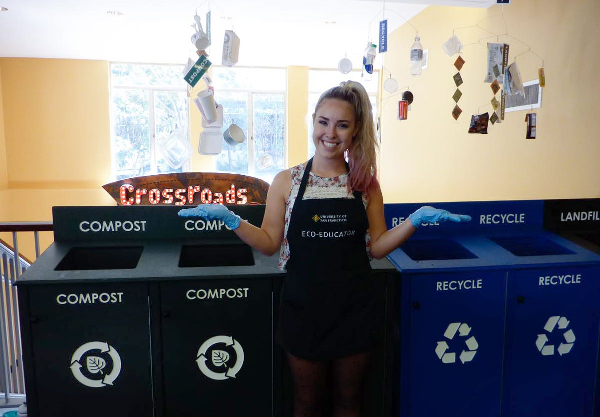 USF student Kathleen Shelton helps guests sort their waste into the right bin