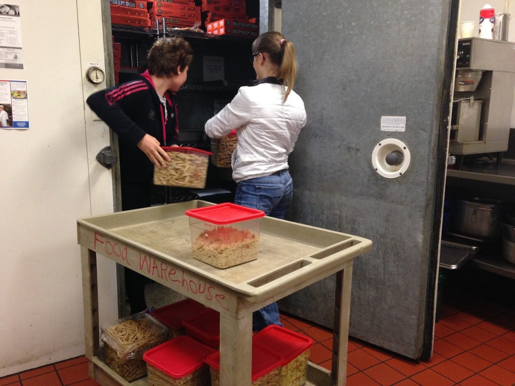 Unloading the food into the Union Gospel Mission's walk-in refrigerator