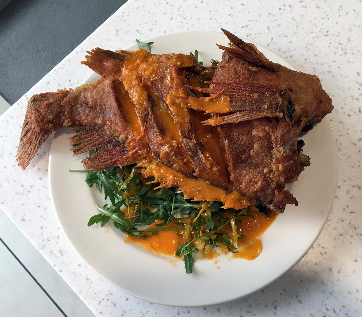 A whole fried fish served at Samsung by our Executive Chef Nicolai Tuban