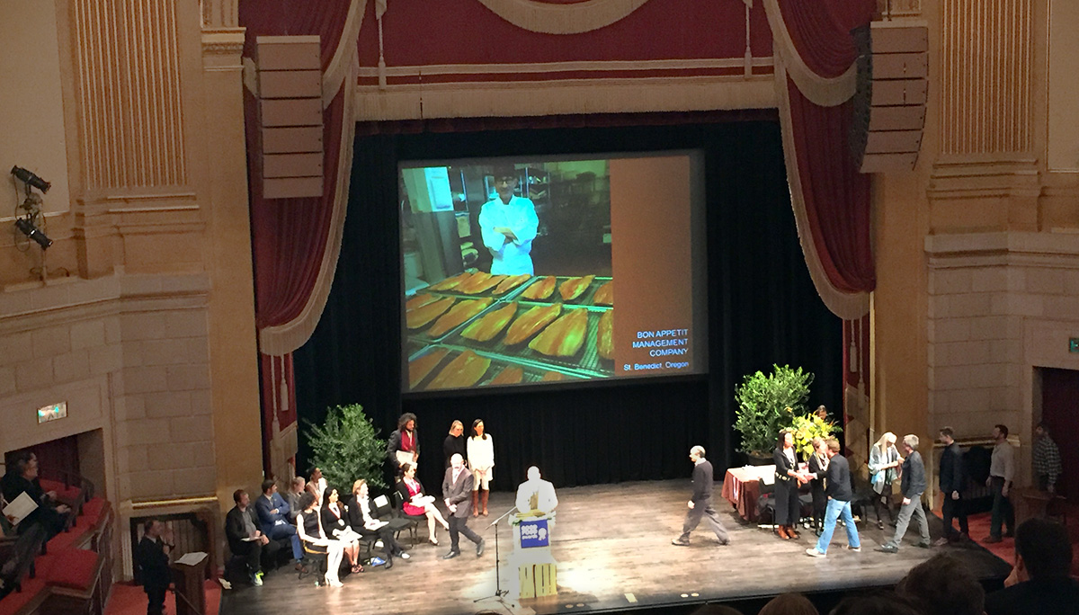 Paul Lieggi walks across the stage after accepting his medal from celebrated restaurateur Alice Waters