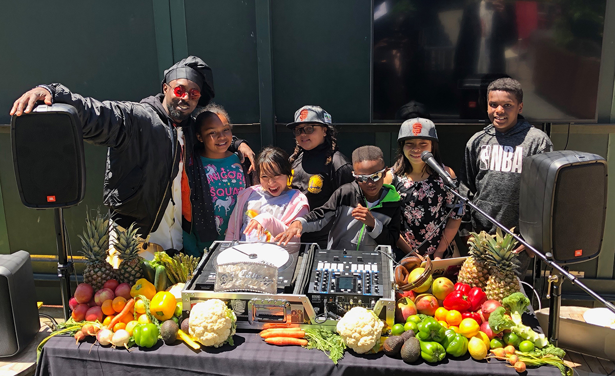 DJ Cavem poses behind his produce-covered DJ booth with students from Enchantment Institute