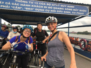 Maisie and Linh on bikes aboard a ferry