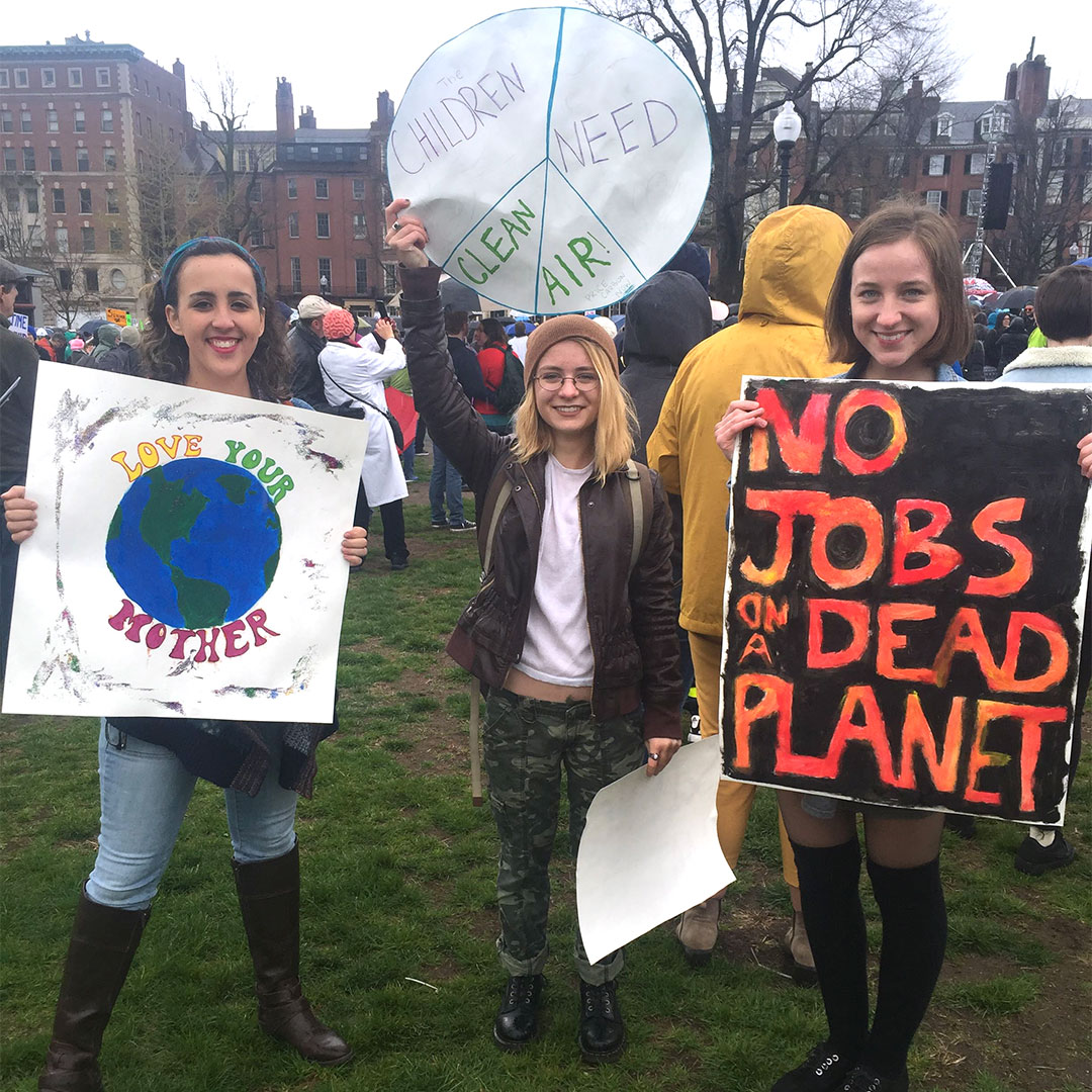 Three young women with protest signs at the 2016 March for Science