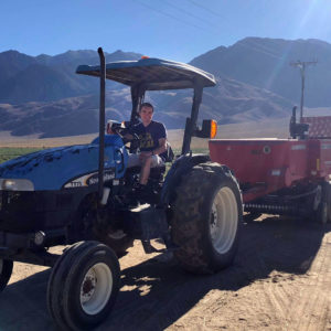 Sam driving a tractor with a hay baler