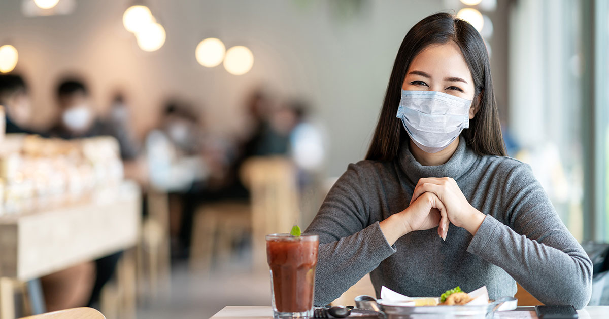 Young woman at restaurant table in mask