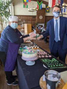Woman hands cupcake to man in suit