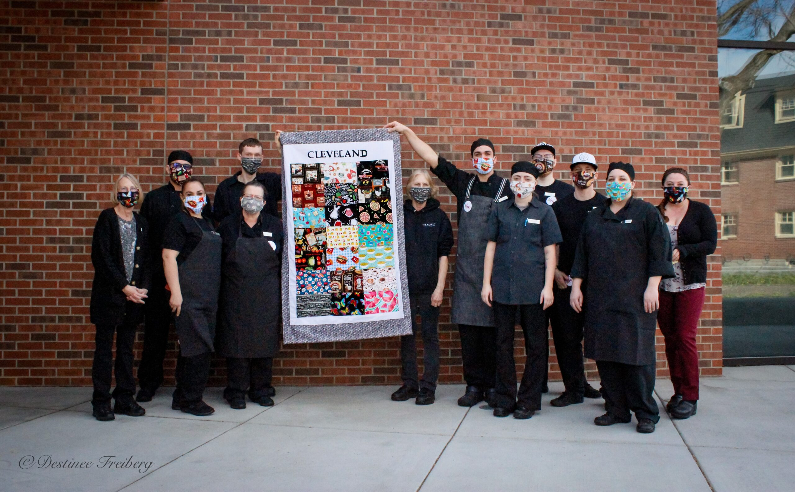 Dining services staff poses with a commemorative quillt