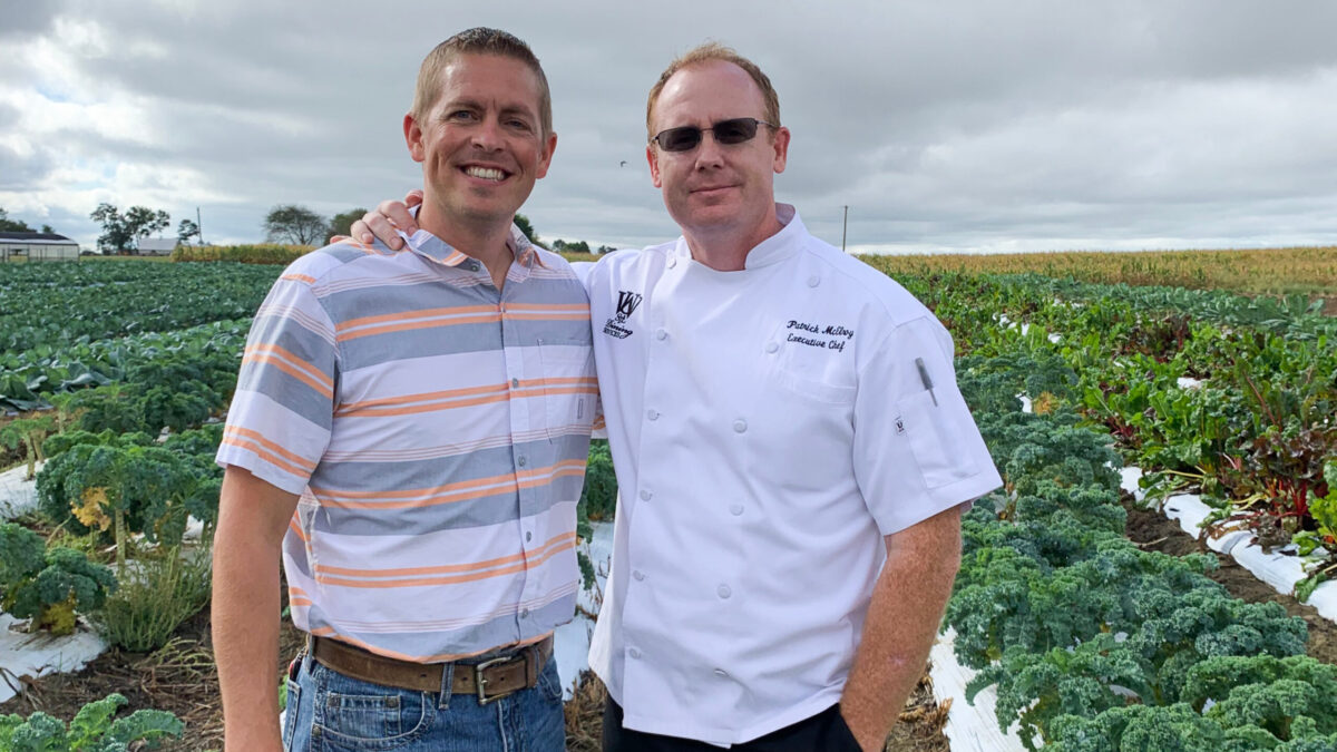 Chef poses with farmer in field