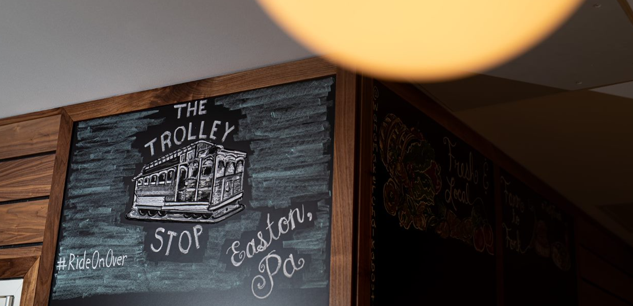 """Chalk art on a wall that says """"The Trolley Stop"""""""