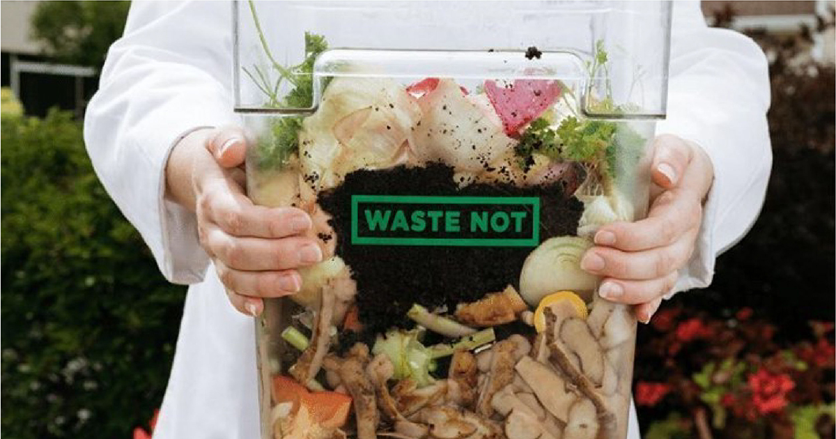 """Clear container holding compostable waste with words """"Waste Not"""" on it."""