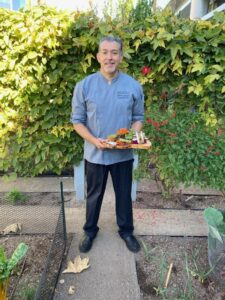 Bon Appétit at Capital Group Executive Chef Alberto Gonzalez poses with a dish he created using garden-grown produce.