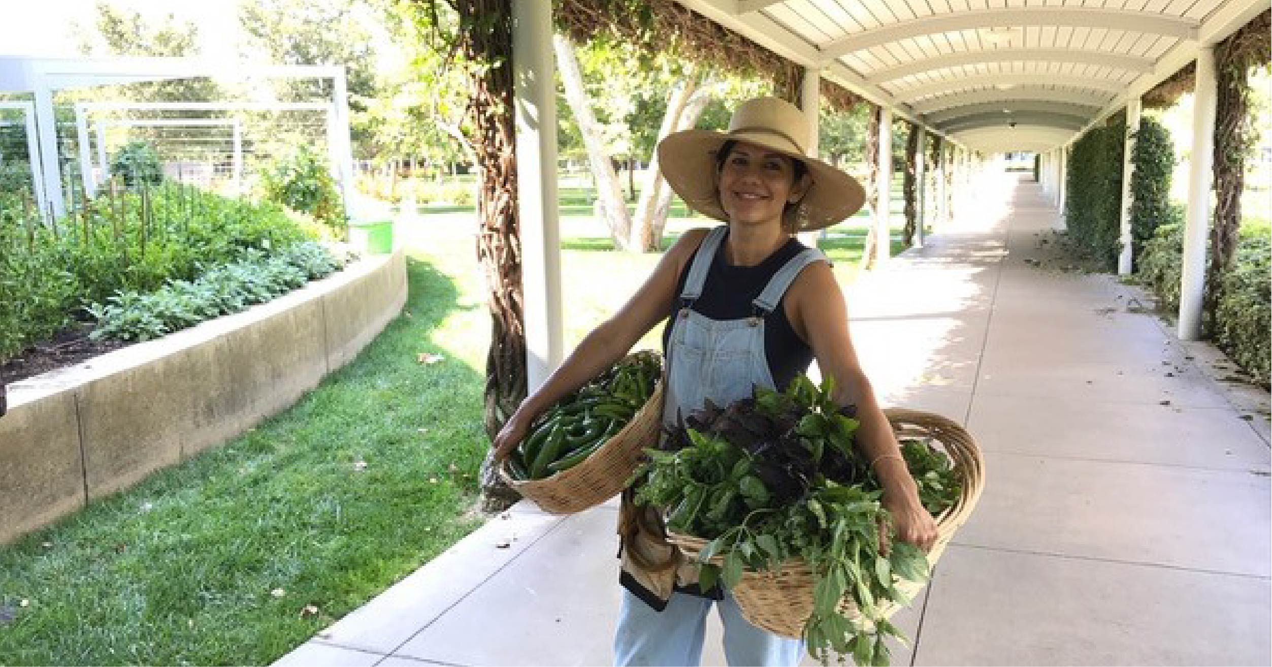 Emy Terusa of Tenfold Harvest poses with a bounty of produce grown in Capital Group's on-site garden in Irvine, CA. A close relationship between Capital Group, Tenfold Harvest, and Bon Appétit brings hyperlocal produce to the menus at Capital Group's on-site café throughout the year.