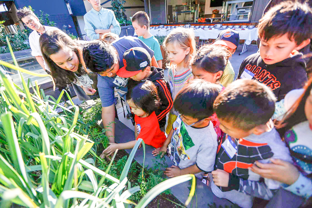Bon Appétit Community Development Manager Hannah Schmunk shows a group of visiting kids how carrots grow