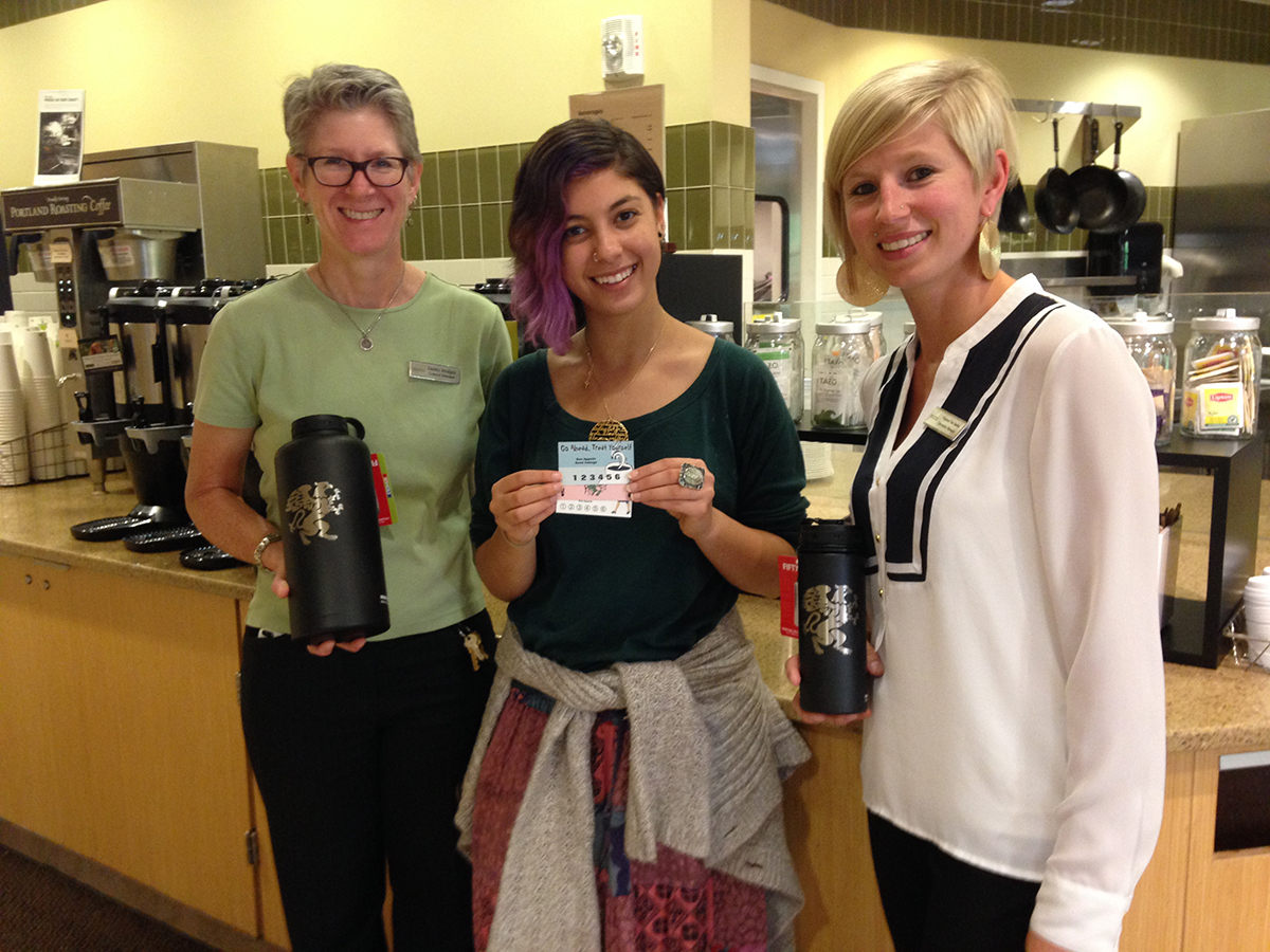 General Manager Debby Bridges, Reed Student Sustainability Coordinator Liat Kastner, and Operations Manager Vanessa van Staden pose with the reusable beverage containers and punch cards
