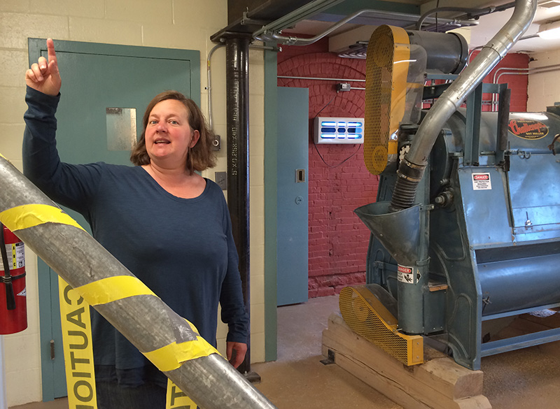 Maine Grains cofounder Amber Lambke shows how grains flow between floors in metal tubes