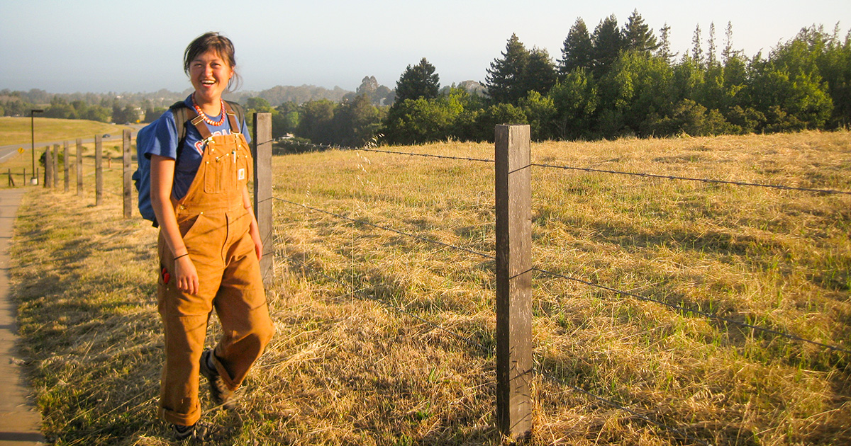 Young woman in field wearing overalls