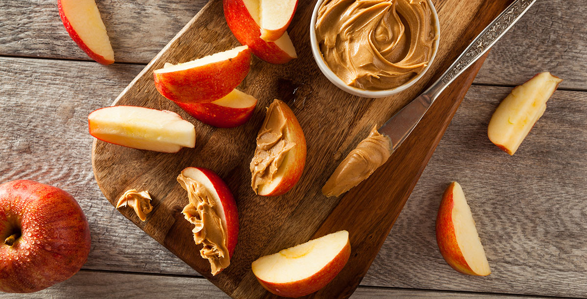 cut-up apples with a jar of peanutbutter and a knife
