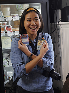 Student Danielle Lee holding up stickers from Zingerman's Creamery