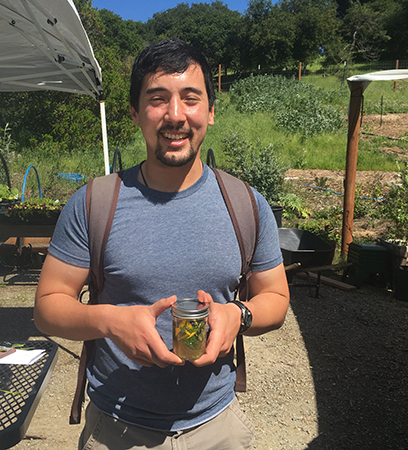 Fellow Taiyo Scanlon-Kimura with a Mills Campus Farm tonic of freshly picked herbs and apple cider vinegar